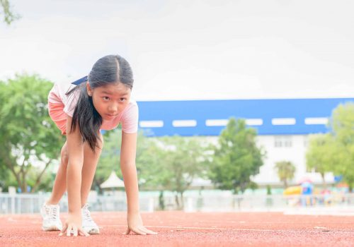 Cheerful cute girl in ready position to run on track,